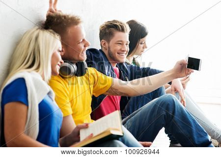Group of happy students being on a break taking selfie. One of students is doing prank. Focus on a happy boy. Background is blurry.