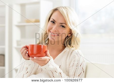 Attractive smiling girl enjoying the smell of coffee in the morning.