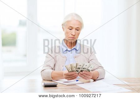 business, savings, annuity insurance, age and people concept - senior woman with calculator and bills counting dollar money at home