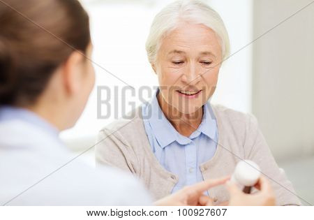medicine, age, health care and people concept - doctor showing pills to happy senior woman at hospital
