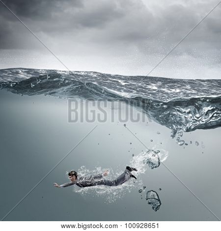 Young businessman in suit swimming in stormy waters