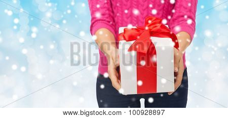christmas, holidays and people concept - close up of woman in pink sweater holding gift box over blue background with snow over blue background with snow