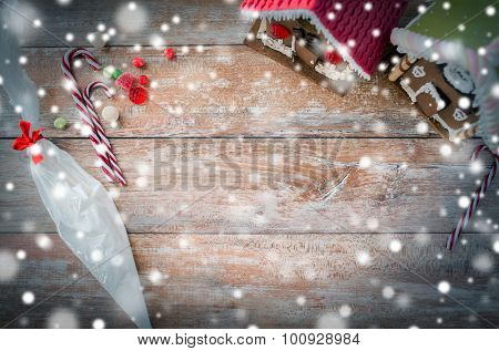 holidays, christmas, baking and sweets concept - closeup of beautiful gingerbread houses and glaze on blank table at home