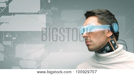 people, technology, future and progress - man with futuristic glasses and microchip implant or sensors over gray background and virtual screens