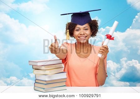 education, school, graduation, gesture and people concept - happy smiling african american student girl in bachelor cap with books and diploma showing thumbs up over blue sky and clouds background