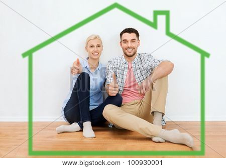 home, people, accommodation, moving and real estate concept - happy couple sitting on floor and showing thumbs up at new place