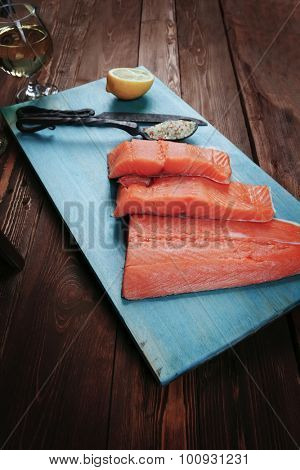 fresh raw salmon fillet served with lemon and white wine in wineglass bottle wooden barrel on blue plate over vintage wood table with forged handmade cutlery knife and  spice on spoon