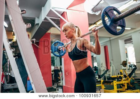 fitness woman doing barbell squats in a gym