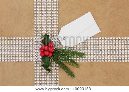 Christmas gift wrapping with diamond bling ribbon, tag and holly over hemp paper background.