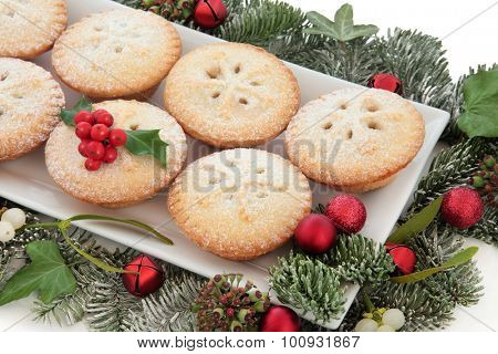 Christmas mince pie cakes on a plate with red baubles, holly, mistletoe and winter greenery over white background.