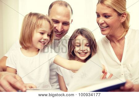 family, childhood, literature and people - happy mother, father and little girls reading book at home