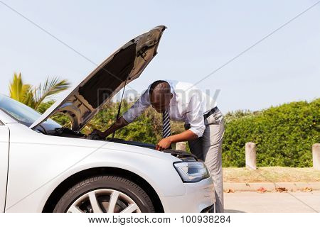 afro american man looking at broken down car engine by side of the road