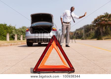 african man looking for help after a car breakdown at the side of the road