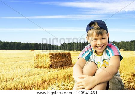 Smiling boy sitting on the stack of hay on the wheat field cloudy sky