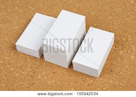 Three Piles Of Business Cards On Corkboard Backgroun.