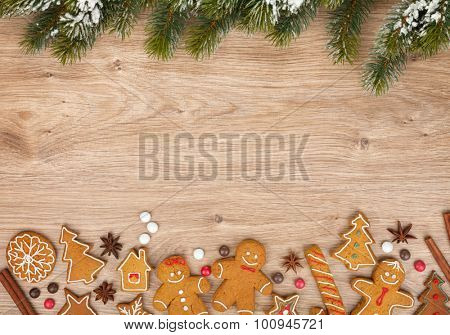 Christmas fir tree and gingerbread cookies on wooden board
