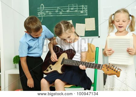 Cute pupils having music lesson in classroom at elementary school