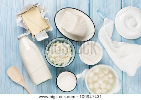 Dairy products on wooden table. Sour cream, milk, cheese, egg, yogurt and butter. Top view