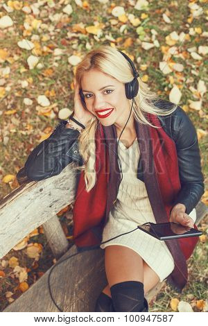Beautiful Blond Listens To The Music Through A Digital Tablet