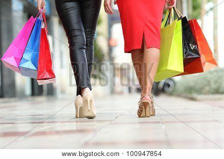 Two Fashion Women Legs Walking With Shopping Bags