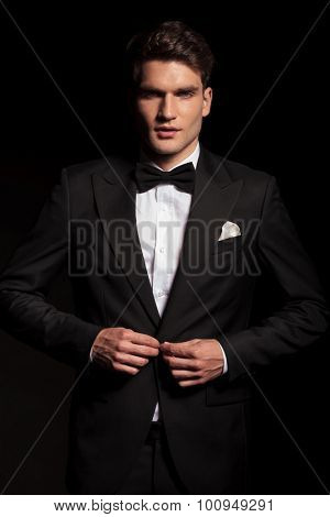 Picture of a young elegant man closing his jacket.