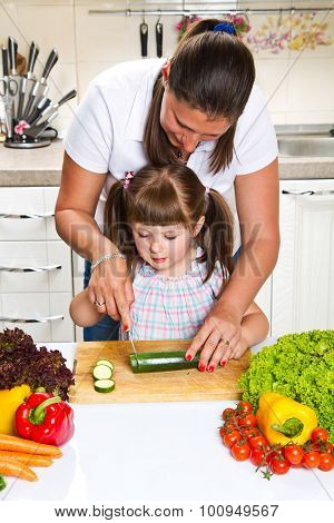 Mother And Daughter In Kitchen Preparing Vegetables