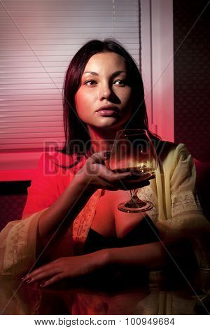 beautiful girl with glass of brandy in cafe