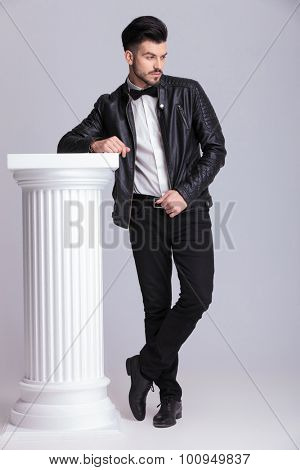 Full length picture of a casual business man leaning on a white column while looking down.