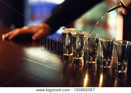 Bartender is pouring tequila into glass