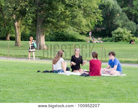 NEW YORK,USA- AUGUST 19,2015 : Young friends camping at the Great Lawn  at Central Park in Manhattan