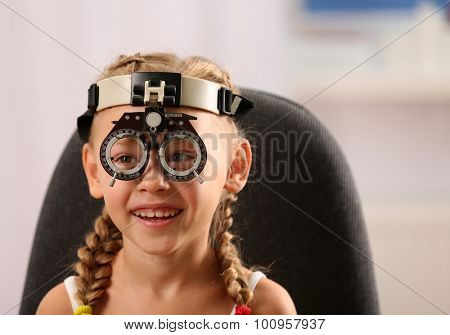 Young girl undergoing eye test with phoropter on blurred background