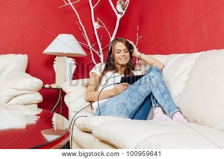 Young Woman Listening To Music Via Digital Tablet On The Sofa