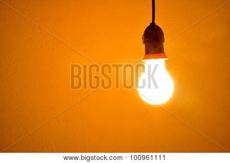 Incandescent light bulb orange light on wall