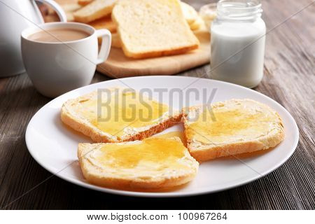 Bread with butter and homemade jam in white plate on wooden table, closeup