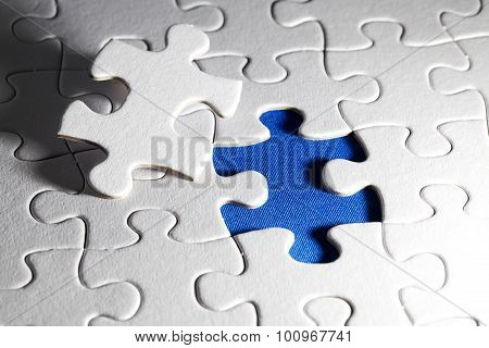 Plain white jigsaw puzzle, on Blue background, autism awarness
