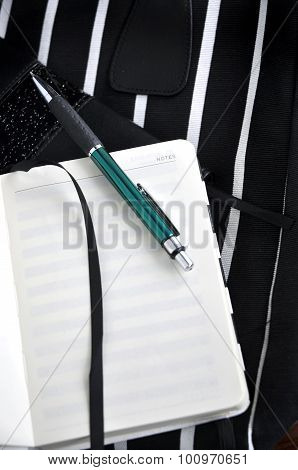 Notebook With Pen On Stripes Background