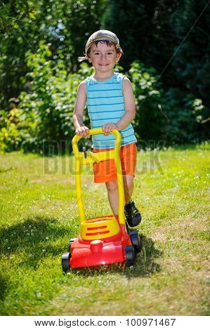 Happy Small Boy Help With Gardening With His Lawn Mower