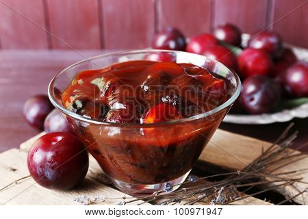 Tasty homemade plum jam in glass saucer on wooden board, closeup