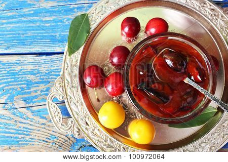 Tasty homemade plum jam in lass saucer on metal tray, top view