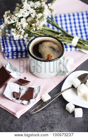 Cup of flavored coffee with chocolate on table with napkin, closeup