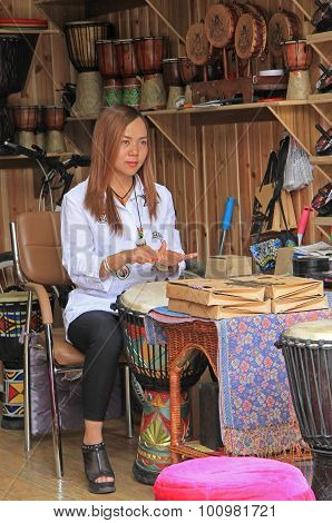 woman is playing djembe on the street in Lijiang, China