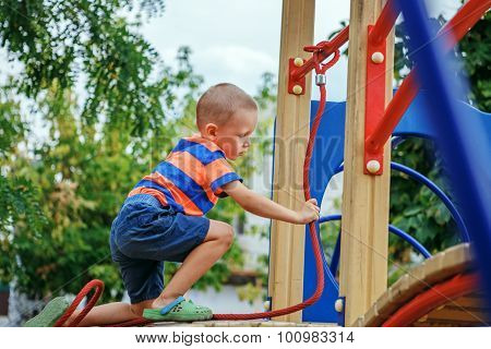 Cute Little Boy Playing On The Playground In The Summer