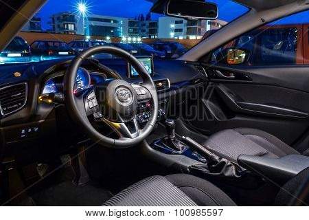 POLAND-SEPTEMBER 24, 2014: Interior of new Mazda 3 captured at dusk with long exposure technique. Mazda 3 is a popular compact car manufactured in Japan by the Mazda Motor Corporation.