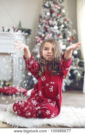 5 years old cute little girl playing with faux snow under decorated Christmas tree at home