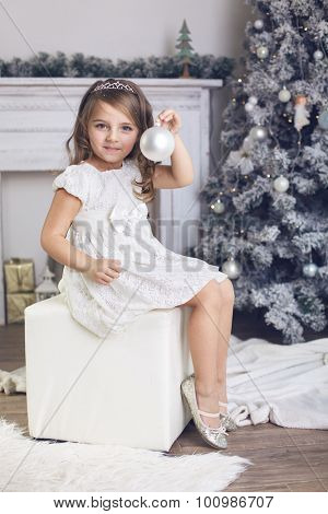 5 years old little girl dressed in beautiful fashion white flower dress holding toy and sitting near Christmas tree