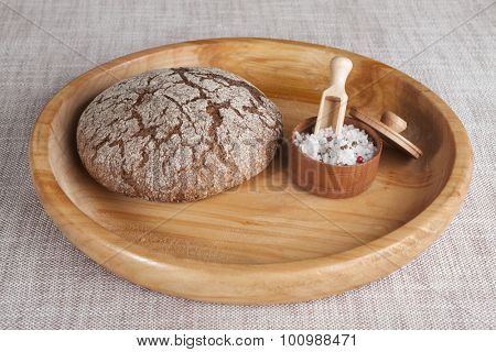 Fresh homemade bread made from durum wheat, rye, on a wooden tray with a jar of salt. Composition on a beautiful tablecloths canvas. Photos for magazines about cooking, confectionery, cooking.