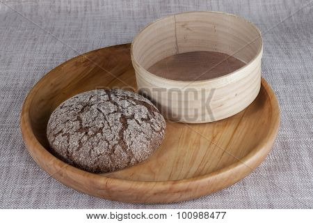 Fresh homemade bread made from durum wheat, rye, on a wooden tray with a sieve for flour . Composition on a beautiful tablecloths canvas. Photos for magazines about cooking, confectionery, cooking.