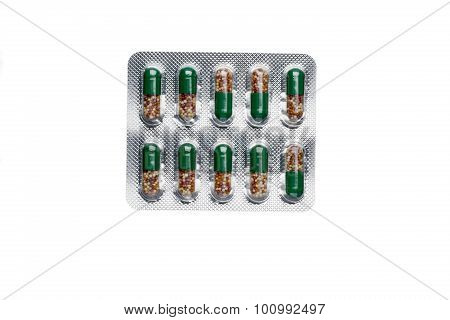 Blister pack of green capsules with micro granules macro view