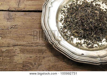 Loose Black Tea On A Silver Plate On Rustic Brown Wood