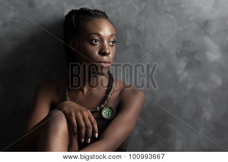 Black Woman With Ethnic Necklace Looking To The Right;